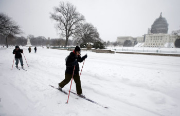 Two people use cross country skis to get around the snow in front of the U.S. Capitol, Saturday, Jan. 23, 2016 in Washington. A blizzard with hurricane-force winds brought much of the East Coast to a standstill Saturday, dumping as much as 3 feet of snow, stranding tens of thousands of travelers and shutting down the nation's capital and its largest city. (AP Photo/Alex Brandon)